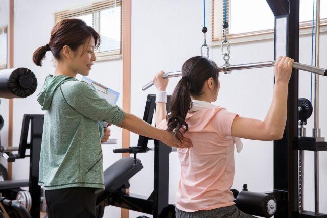 パーソナルトレーニングジムでトレーニングを受ける女性